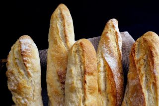 Five Baguettes sitting in a basket